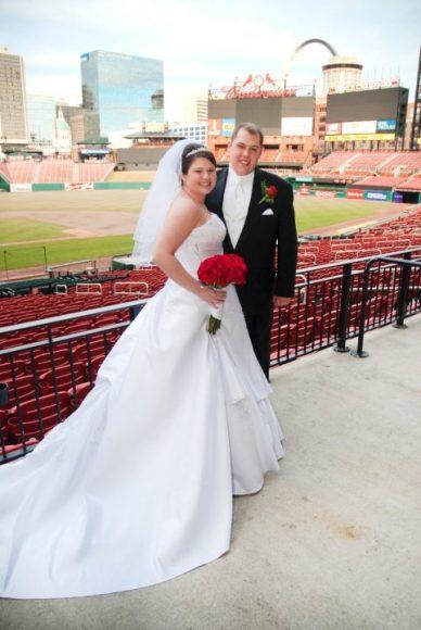 A couple on their wedding day having photos taken at Cardinals stadium.