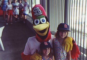 Fredbird, the St. Louis Cardinals mascot, posing with two young girls in the 1990s
