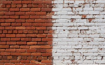 A brick wall. Left half of the image is red brick, right half is painted white.