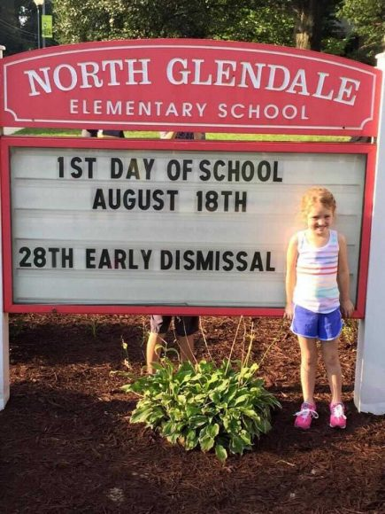 an incoming kindergarten girl standing next to the North Glendale elementary school sign, as she gets ready for the first day of school
