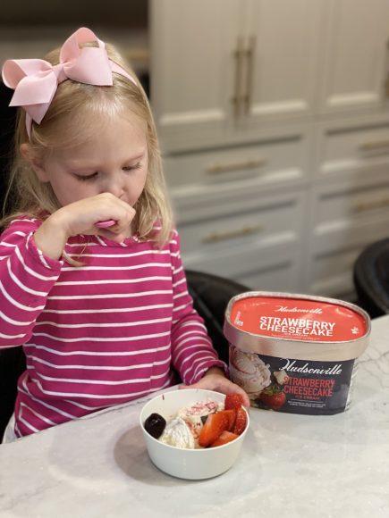 Girl eating Hudsonville Strawberry Cheesecake Ice Cream