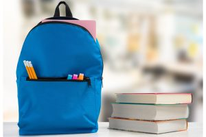a new backpack filled with school supplies on a table next to a stack of books
