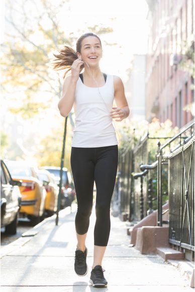 a woman in a white tank and black leggings running down the sidewalk as she adjusts her EarPods