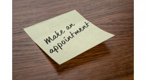 """a sticky note on a wooden table that says, """"make an appointment"""""""