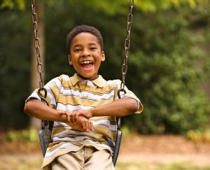 an African American boy on a swing at a playground