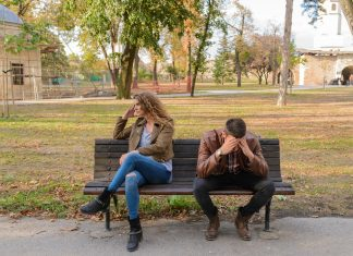 a man and a woman sitting on a bench, their body language showing their frustration as she turns away and he holds his head in his hands