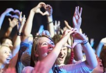 an adoring crowd of fans making hearts with their hands for the musicians on stage