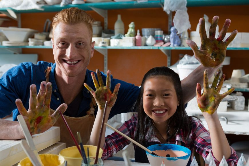 a girl and a man painting pottery, with their hands raised and covered with paint