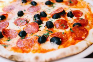 a close up of a wood fired pizza with pepperoni and black olives