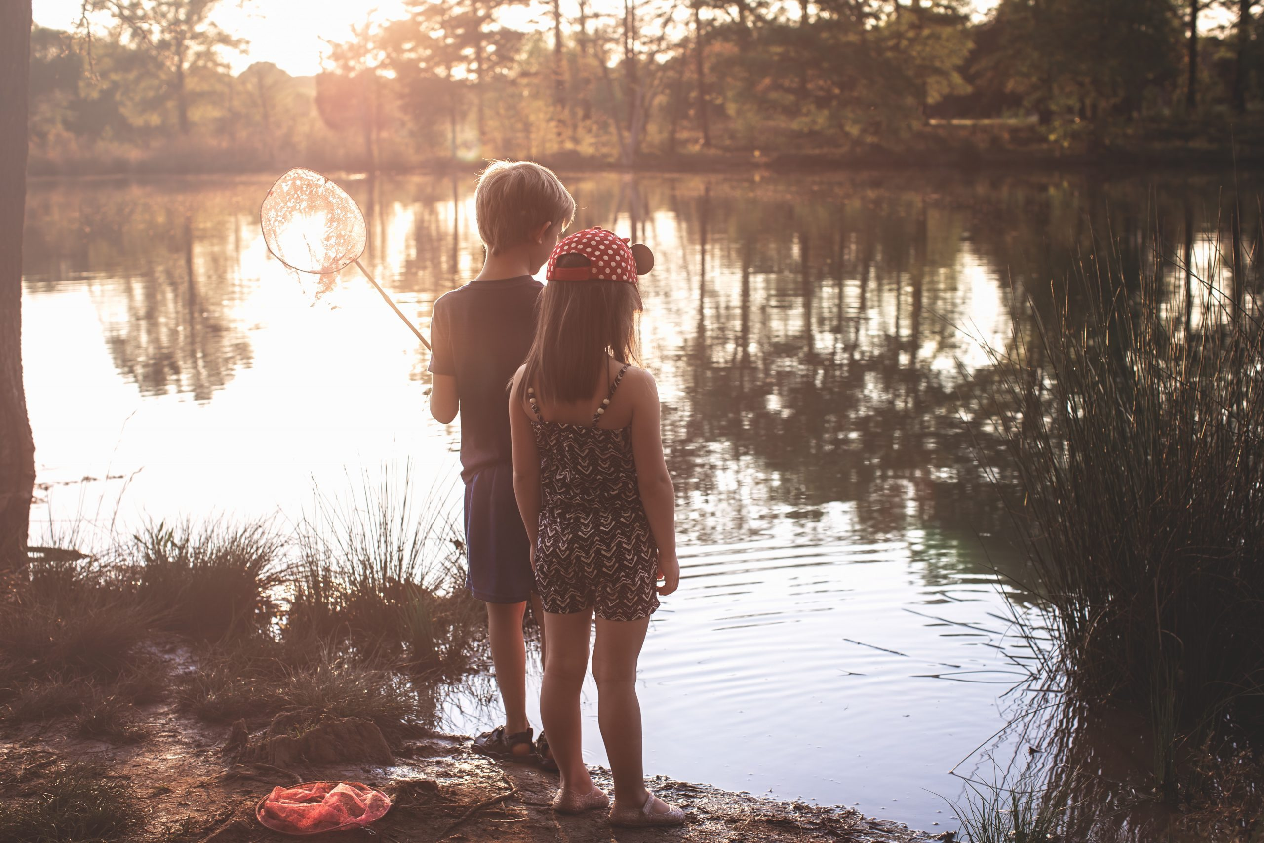 a picture of a girl and a boy holding a fishing net at the edge of a lake