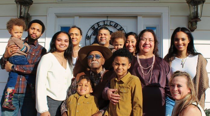 a multigenerational family standing on a porch for a family photo honoring National Sandwich Generation Month.