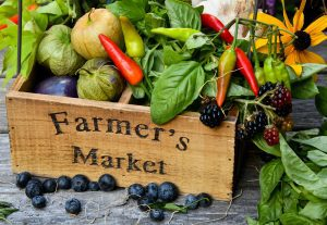 """a wooden crate etched with the words, """"Farmer's Market"""" and filled with produce and flowers to represent the Kirkwood Farmer's Market"""