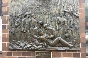 a plaque on a brick wall in New York City honoring the first responders of the NYPD and NYFD and their sacrifice on September 11th