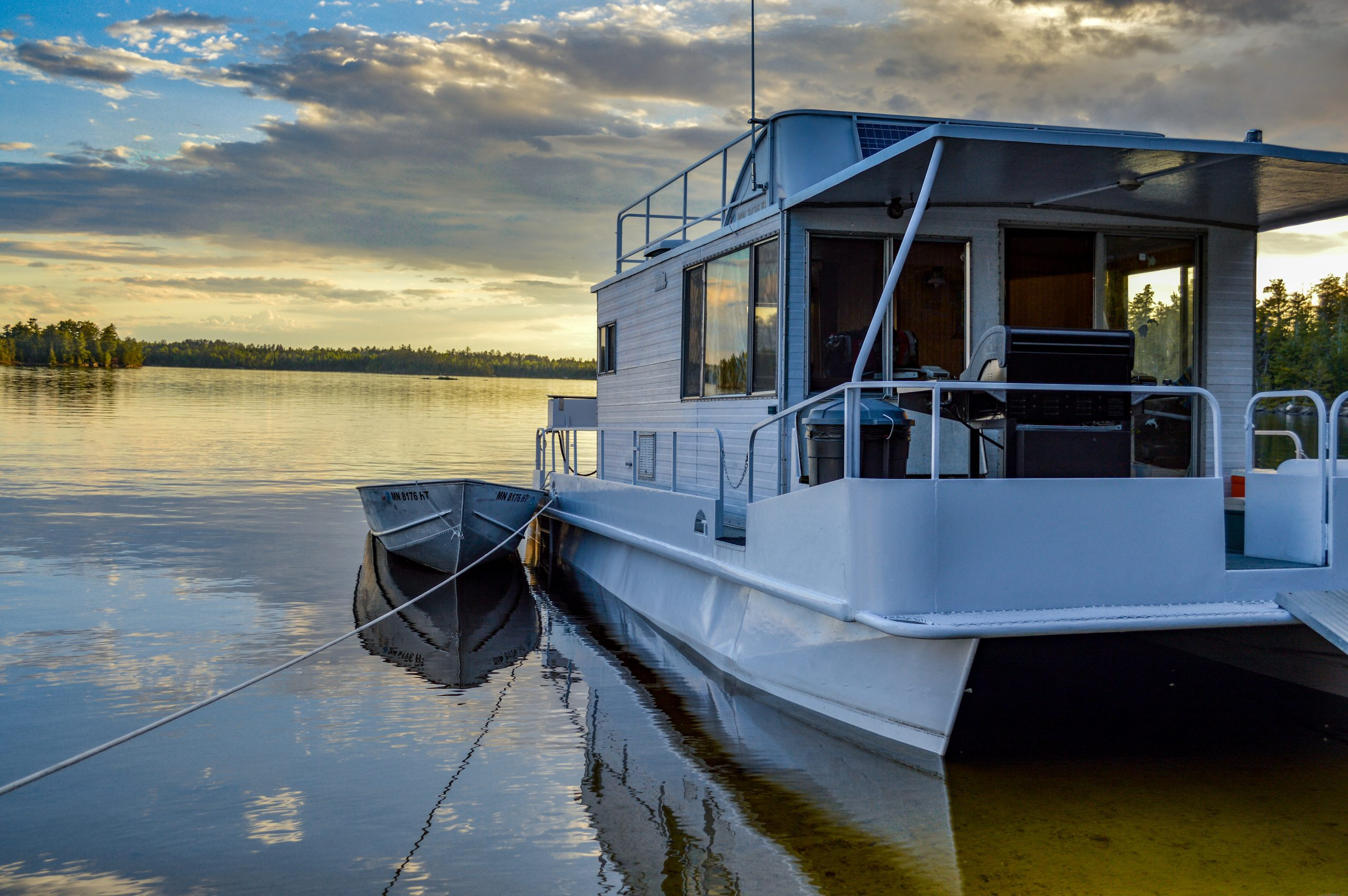 a houseboat on a lake as the sun is setting