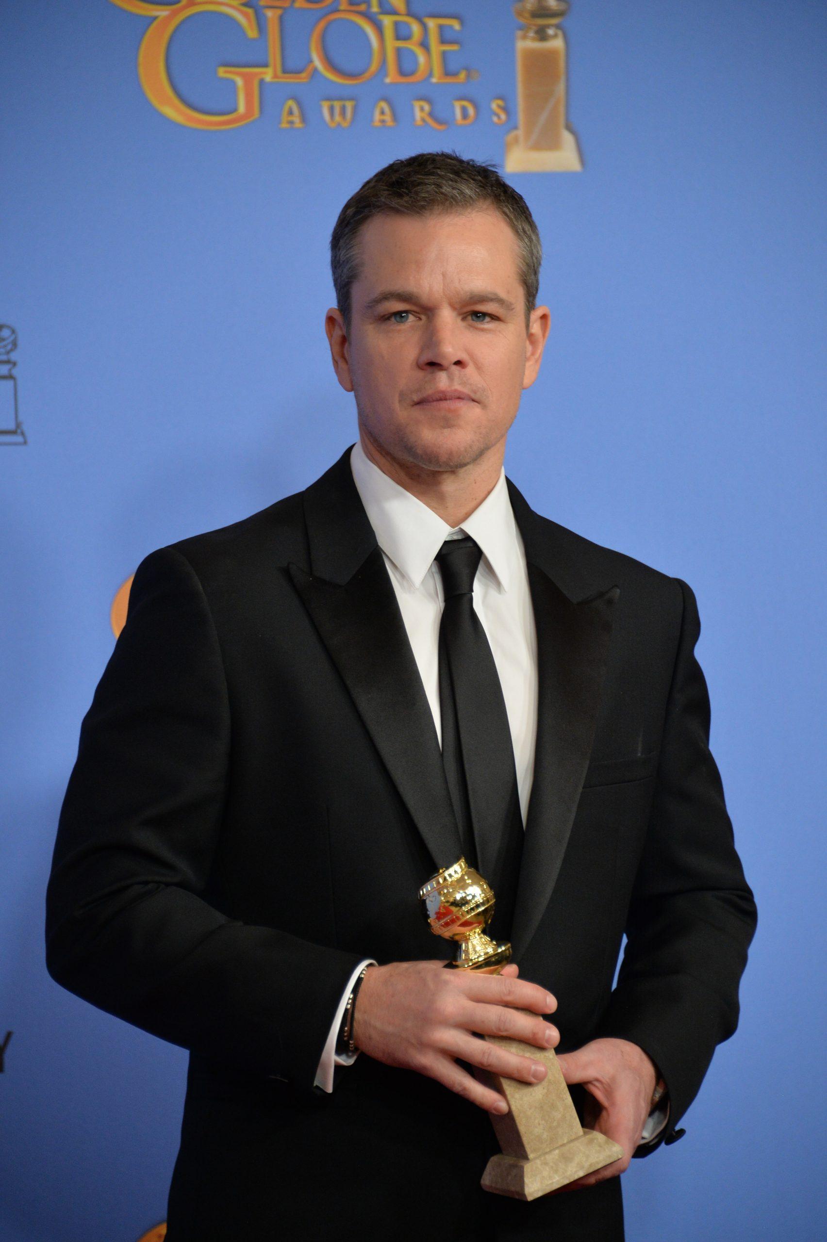 Matt Damon holding a Golden Globe
