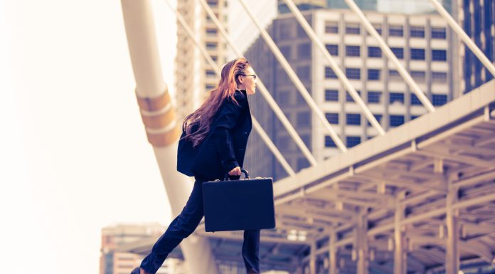 a business woman crossing a road with her briefcase in a return to work