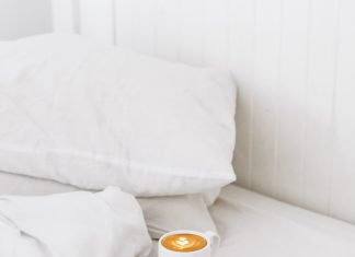 a bed of white linens and pillows, with a mug of coffee, a book, and glasses set on the comforter to represent self-care