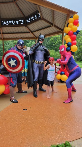 Captain America, Batman, and Spiderman pose with a young boy at STL Mom's Hanging with Heroes event