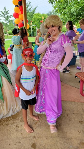 super heroes and princesses visited an event as a young boy poses for a picture