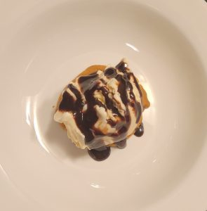 a warm chocolate chip cookie topped with Hudsonville Ice Cream and chocolate sauce