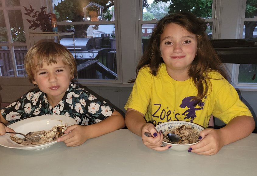 a boy and a girl sitting at a counter as they enjoy bowls of Hudsonville Ice Cream