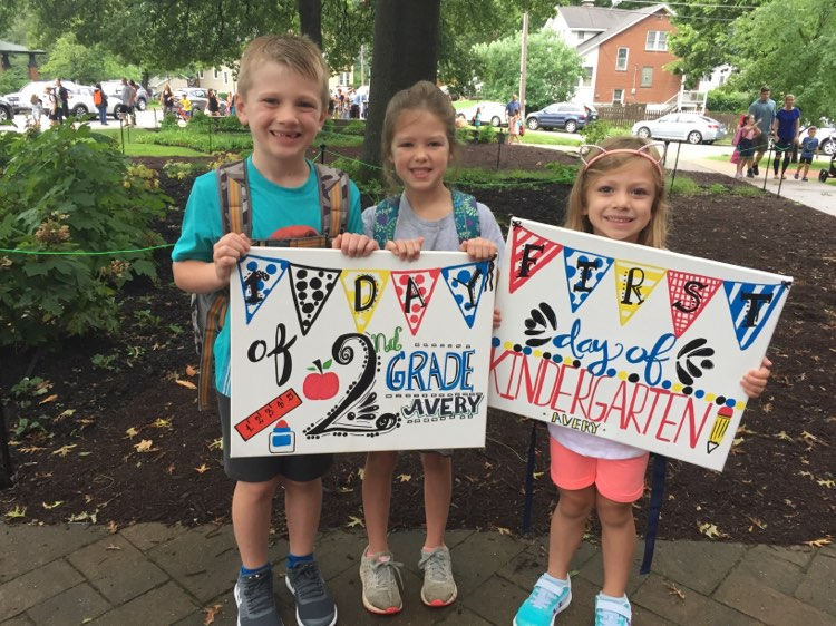a boy and two girls holding first day of school signs