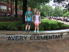 a boy and a girl posing at their elementary school on the first day of school