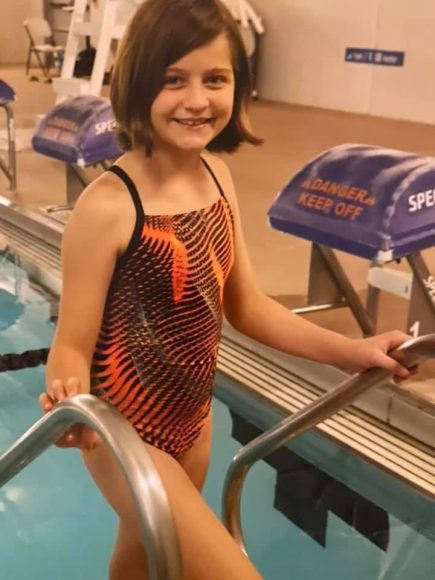 a girl smiling as she climbs out of the pool during a swim meet where she learned good sportsmanship