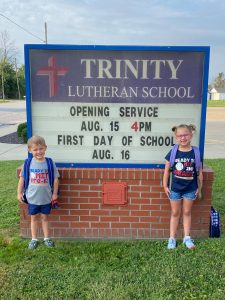 a young boy and his sister standing by the school marquee board for the first day of school