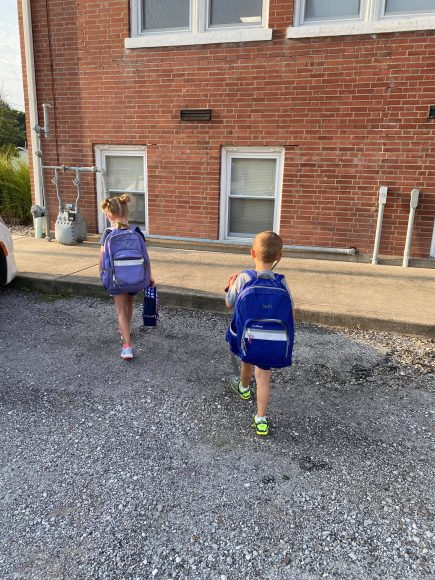 a young girl and her brother, wearing big backpacks as they head back-to-school