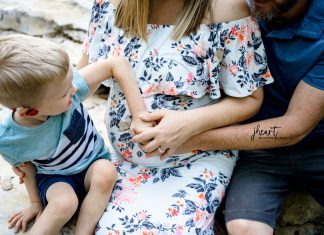 a little boy putting his hand on his mom's pregnant belly as she gets ready for a C-section
