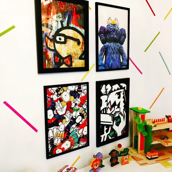 a brightly colored wall of art by favorite artists for kids' spaces