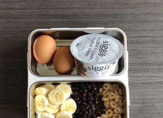 a bento box with banana slices, hard boiled eggs, yogurt, and cereal for feeding children healthy food