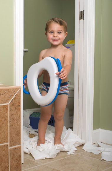 a toddler boy standing in a bathroom doorway, surrounded by unspooled toilet paper, and holding a potty seat