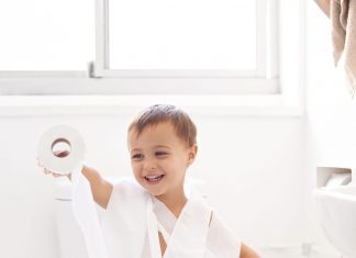 a toddler boy wrapped in toilet paper as he sits on the toilet