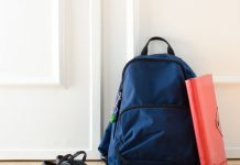 a navy blue backpack sits by a closed door, with a red notebook leaning on it and a pair of shoes nearby getting ready for back-to-school