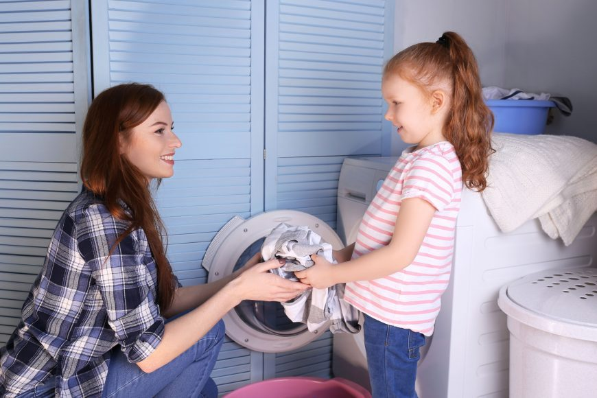 a girl helping her mother do laundry