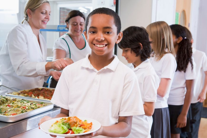 a line in the lunchroom of kids being served lunch