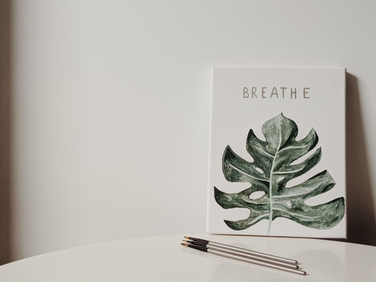 """a canvas on a table with the painting of a green leaf and the word, """"Breathe"""" above it reminding us that it is okay to step back"""