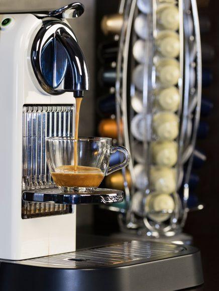 an espresso machine on a countertop, brewing a pod of espresso