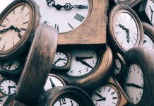 time management represented by a pile of analog clocks with dark wooden frames