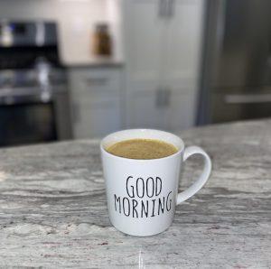 """a white mug full of PSL that says, """"good morning"""""""