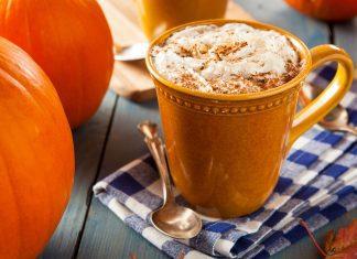 a pumpkin spice latte in a mug on a table next to pumpkins
