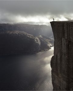 a black and white image of someone standing at the edge of a cliff, symbolic of saving yourself from the edge