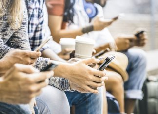a close up of a group of friends, all staring down at their phones