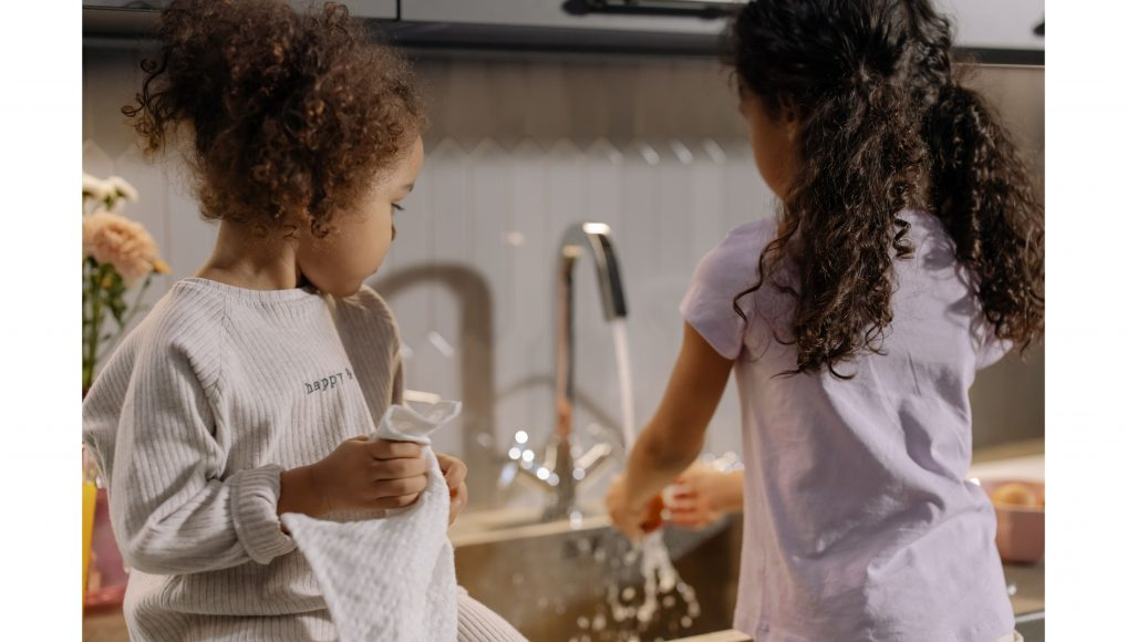 the back view of two girls washing dishes