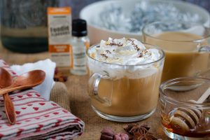 a pumpkin spice latte in a clear mug on a table with vanilla and honey