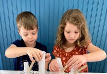 a boy and a girl conducting science activities with leaves using four mason jars with leaves in them and strips of coffee filters