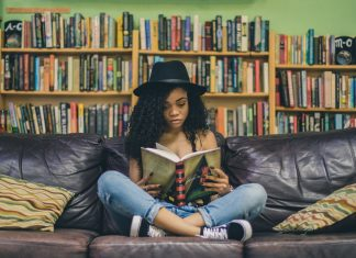 a teen girl sitting on a couch in a library, reading a book