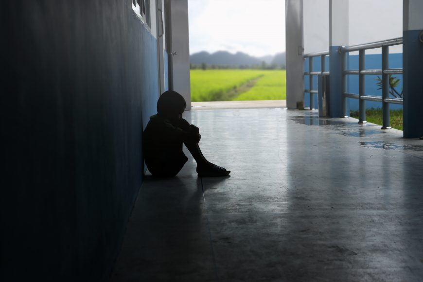 a teen boy sitting in a dark hallway with his hands wrapped around his knees